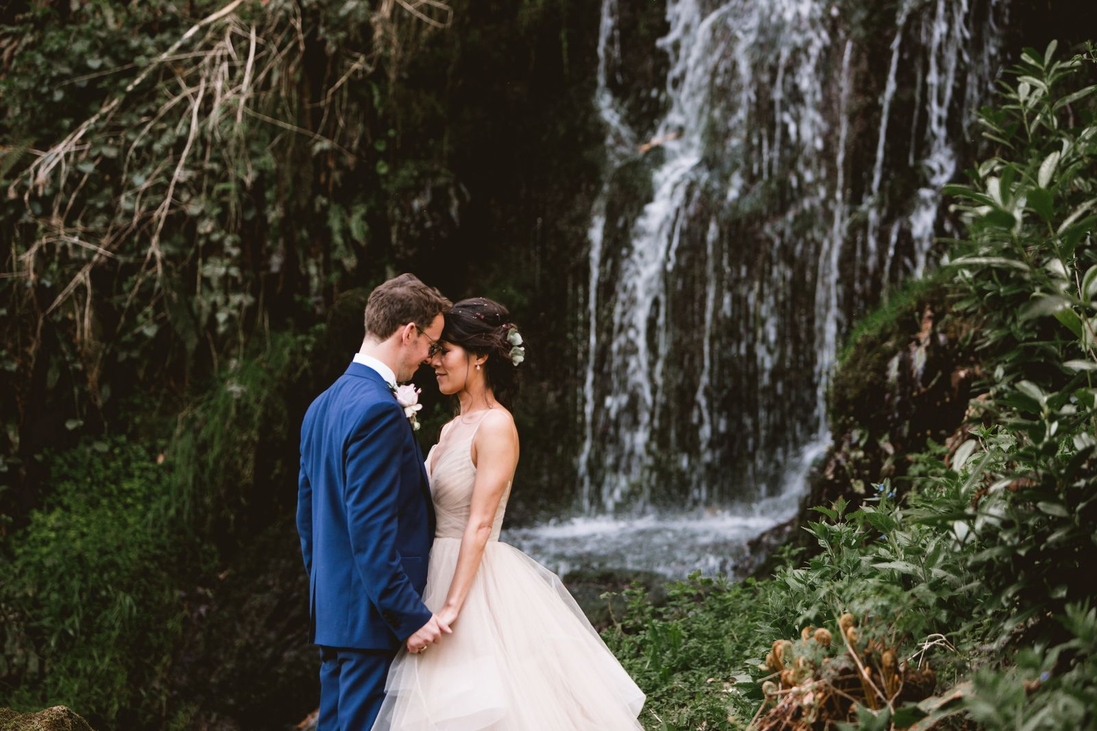 Bride and groom pose together beside the waterfall at Hestercombe Gardens
