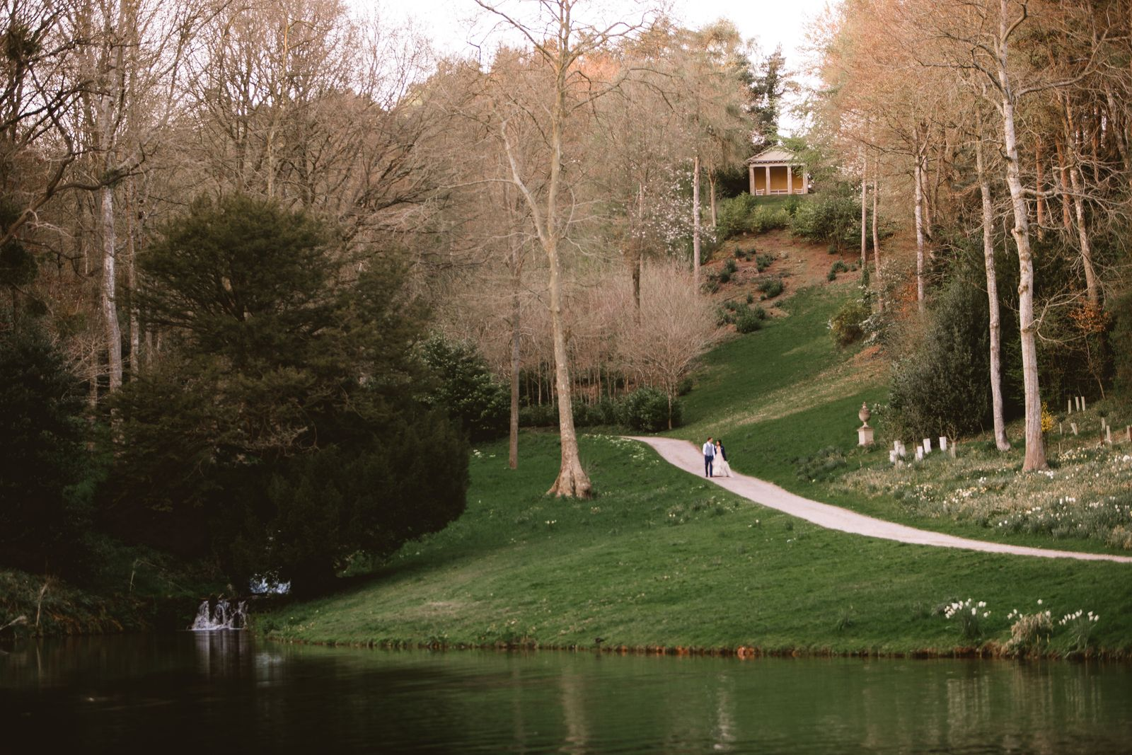 Couple walk along the lake path with the temple behind - the setting for outdoor wedding ceremonies in Somerset at Hestercombe Gardens