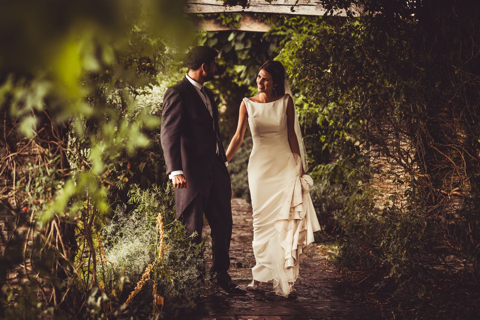 Bride and groom walk hand in hand through the leafy pergola at Hestercombe Gardens wedding