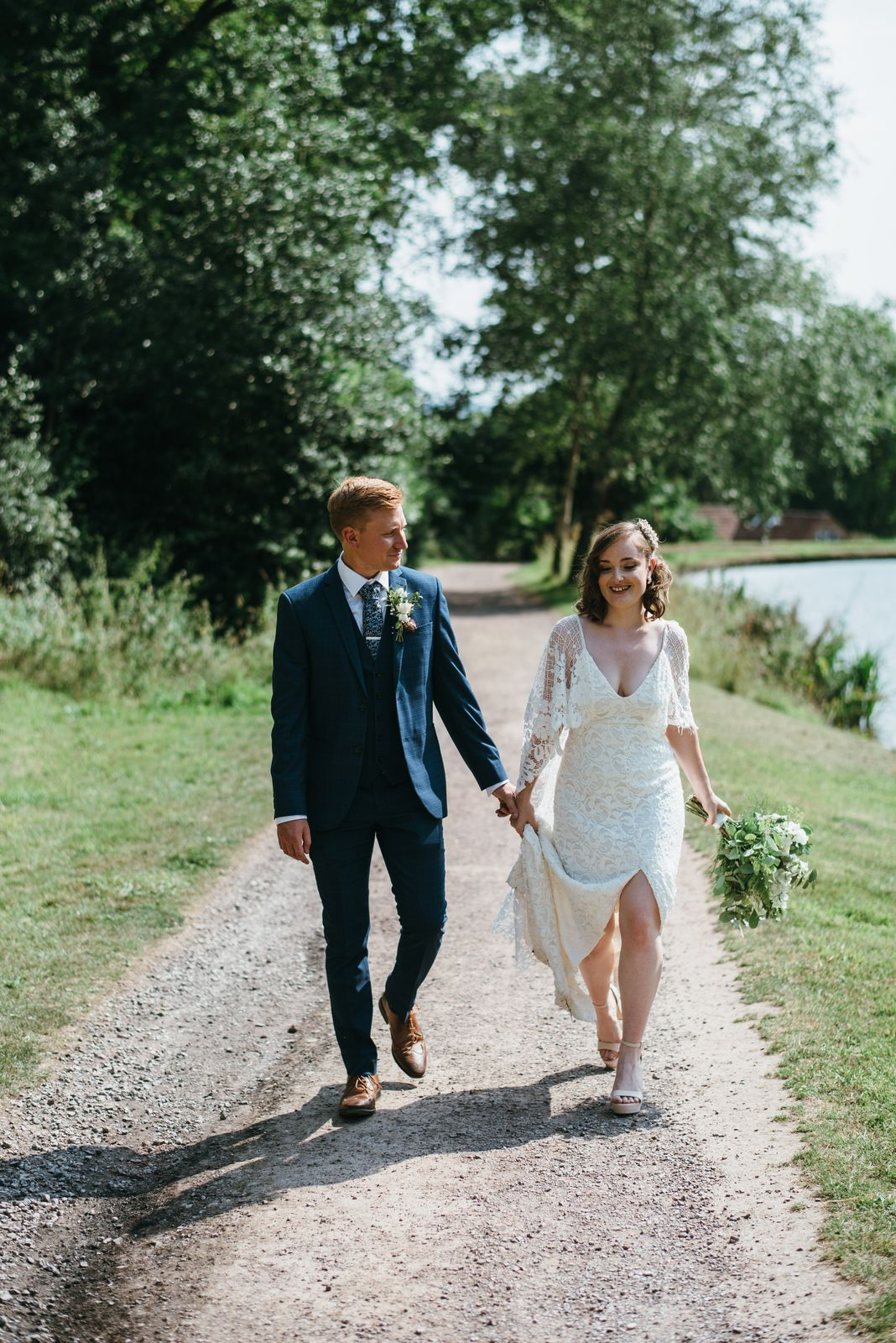 Bride and groom wander in a relaxed manner alongside the lake, hand in hand