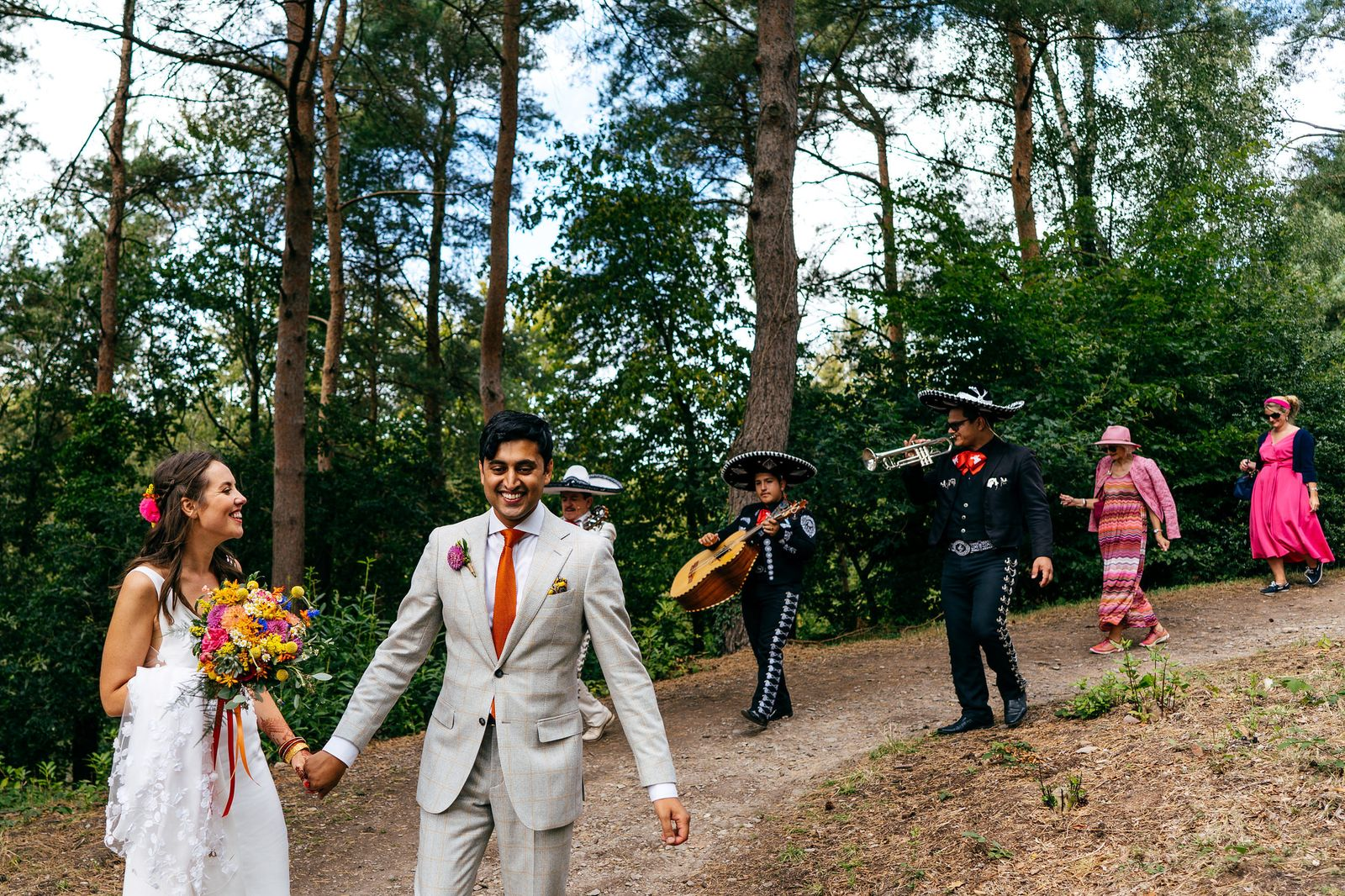 Newlyweds dance down the path at Hestercombe Gardens with musicians