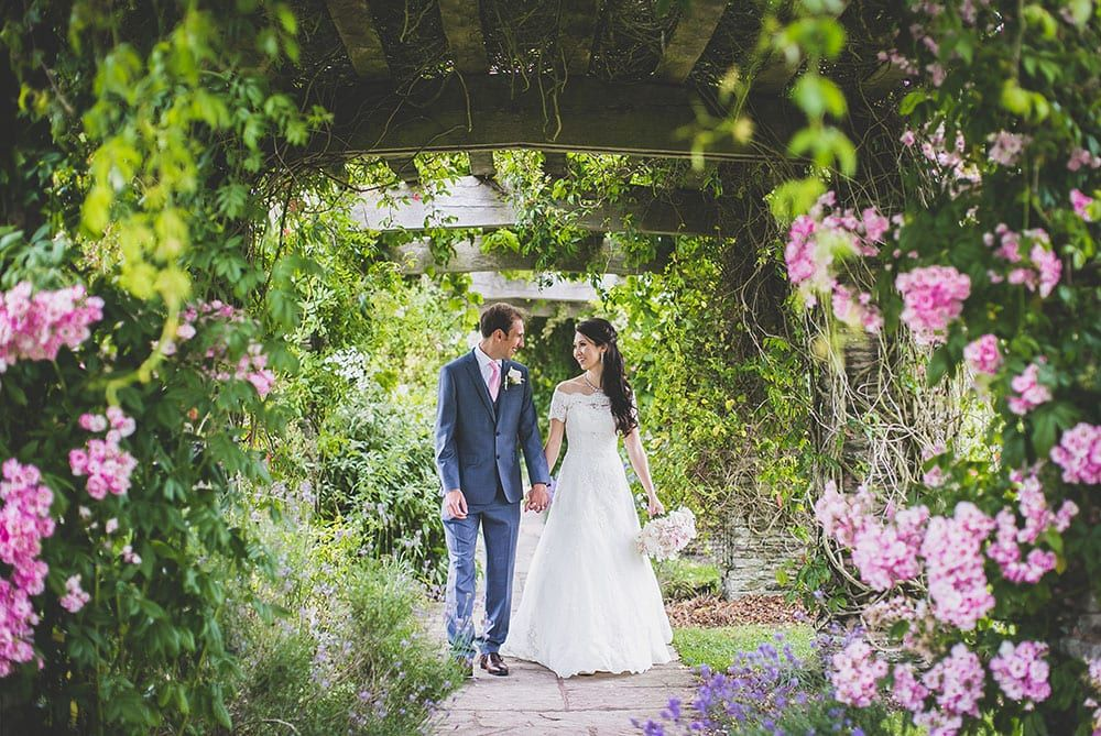 Couple walk through pergola at their Somerset wedding